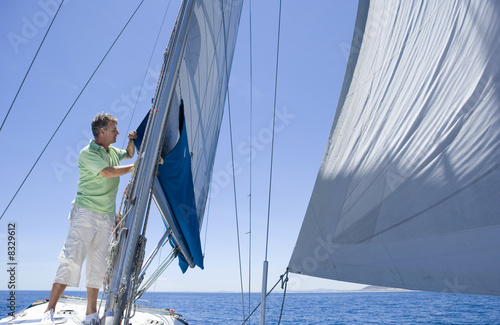 Man standing on deck of sailing boat out to sea, adjusting sail mast rigging, side view