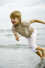 A young boy running on a beach