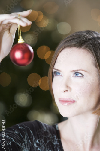 A woman holding a Christmas decoration
