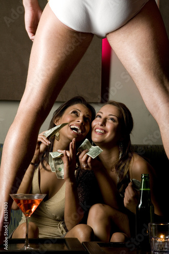 Two young women watching a male stripper