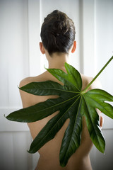 A young woman posing with a tropical leaf
