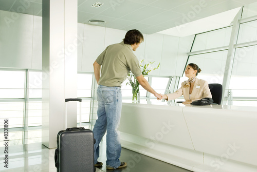 A receptionist greeting a visitor