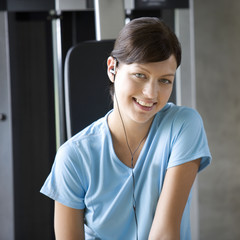 A young woman listening to music in a gym