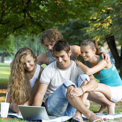 A group of teenage friends with a laptop in a park