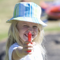A young girl with a water pistol