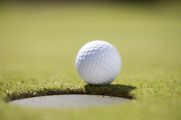 Close-up of a golf ball on the edge of a hole