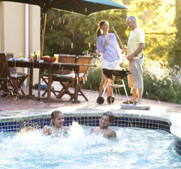 Children swimming in the pool at a family barbeque