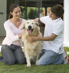 A brother and sister with their dog in the garden