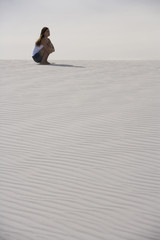 A young woman sitting in the desert