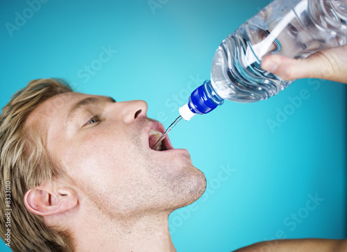 A young man drinking water from a bottle