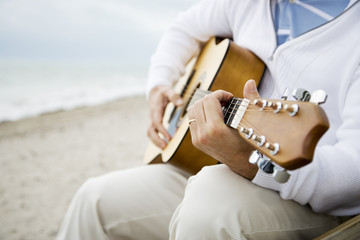 A senior man playing a guitar
