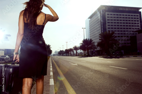 A woman walking on the side of a road