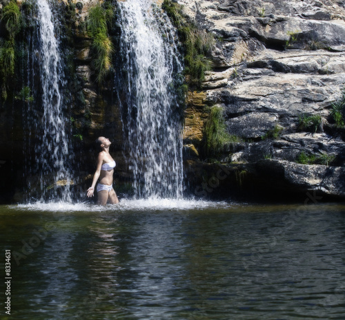 Young woman standing in a waterfall