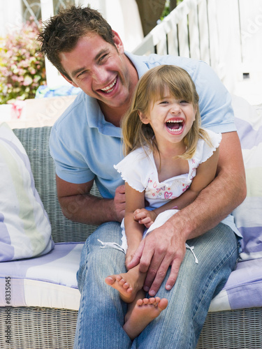 Man and young girl sitting on patio laughing
