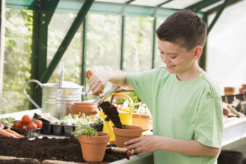 Young boy in greenhouse putting soil in pot smiling