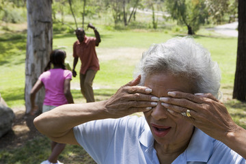 Children (6-10) playing hide and seek with grandparents in park, senior woman covering eyes