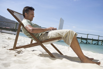A mature man sitting in a deck chair using a laptop