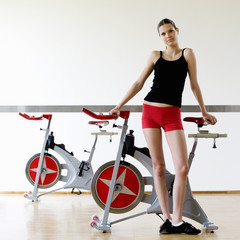 A young woman standing by an exercise bike