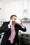 Businessman drinking a coffee and talking on the phone in the kitchen
