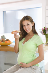 Young pregnant woman holding cream roll, smiling, portrait