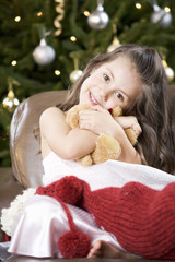 A young girl with a Christmas stocking hugging her teddy bear