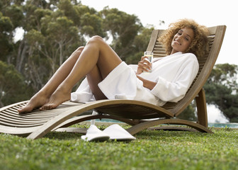 A young woman sitting on a sun lounger