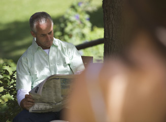 Man sitting in a garden reading a newspaper