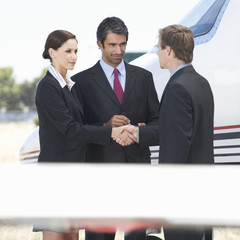Three business colleagues standing by a plane