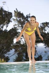 A teenage girl having fun by a swimming pool