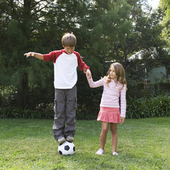 Young boy and girl playing with a football in a garden