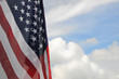 United States flag with partly cloudy sky background