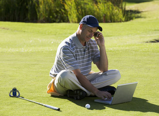 Man using a laptop and mobile phone whilst on the golf course