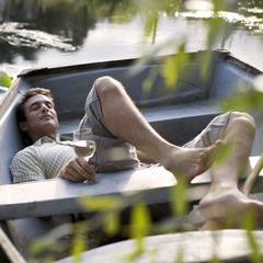 Young man laying in a boat drinking wine