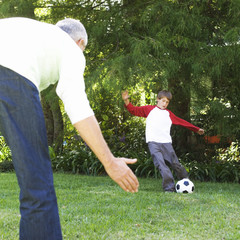 Father and son playing football in a garden