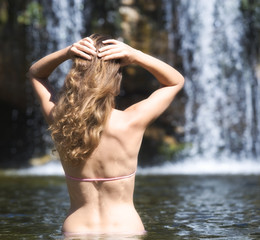 Young woman in a bikini standing in a natural pool
