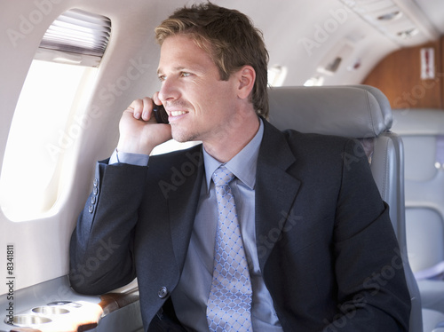 A businessman talking on a mobile phone in a plane