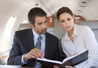 A businessman talking to his PA on a plane