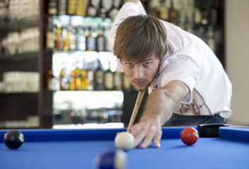 A young man playing pool