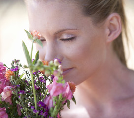 A young woman sniffing a bouquet of flowers, close-up