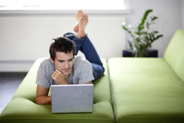Young man with a laptop, laying on a bed