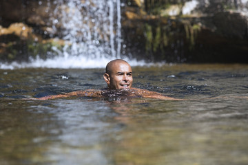 Young man swimming near a waterfall