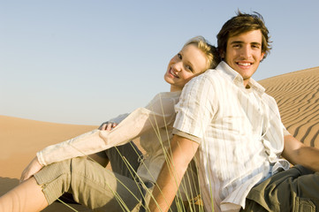 A young couple sitting in the desert