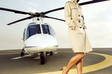 A woman standing by a helicopter