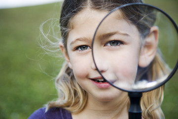 A young girl holding a magnifying glass