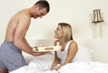 Young couple in bed having breakfast