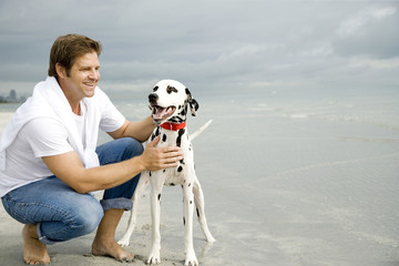 A man with his dog on a beach