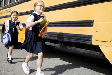 Two schoolgirls running for the school bus