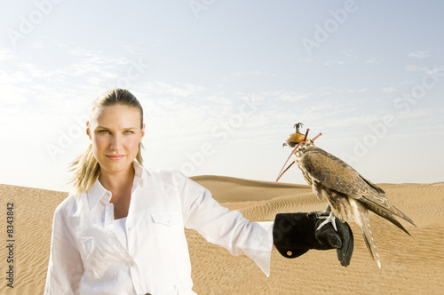 A woman standing in the desert with a hawk