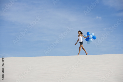A woman walking in the desert holding a bunch of balloons
