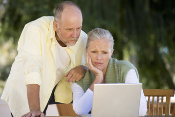 A senior couple working on a laptop
